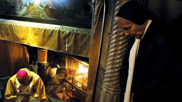 A worshipper praying in the Grotto during the Sunday Christmas Mass at the Church of the Nativity in the West Bank city of Bethlehem, traditionally believed to be the birthplace of Jesus Christ.