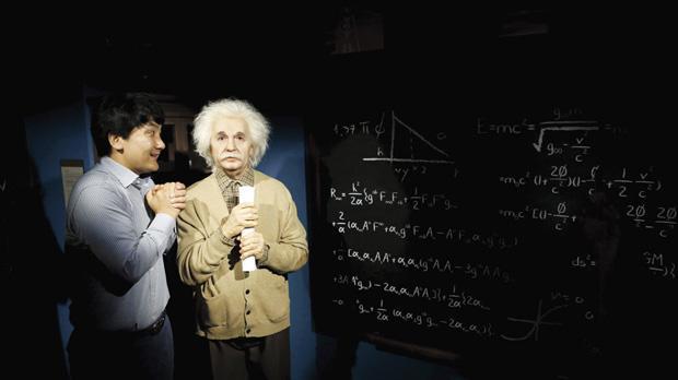 man joking next to the wax figure of Albert Einstein at Grevin Wax ...
