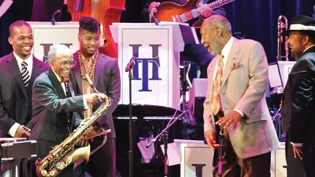 Vibraphonist Warren Wolf, tenor saxophonist Jimmy Heath, trumpet player Christian Scott and actor-comedian Bill Cosby joking about the height of a microphone during the opening.