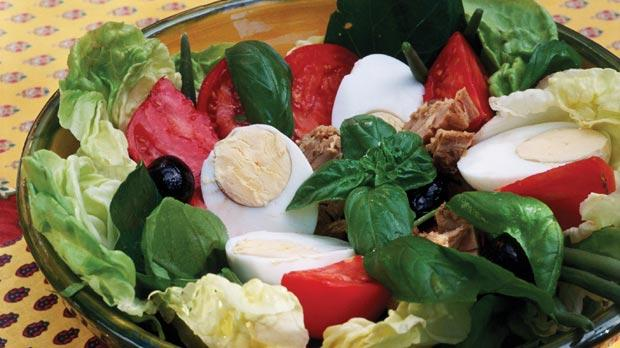 Tomatoes, hard-boiled eggs, salted anchovies, tuna, spring onions, small black Nice olives and basil form the traditional Niçoise salad.