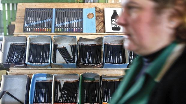 An employee passing by several ColorAdd pencils on display at the traditional Portuguese pencil factory, Viarco, in Sao Joao da Madeira.