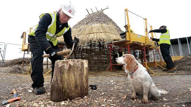Volunteer Richard Hayes is watched by his dog Tigi as he cuts roof supports for the five Neolithic buildings being recreated in the new outdoor exhibition area of the Stonehenge visitor centre in Wiltshire.Photo: Andrew Matthews/PA Wire